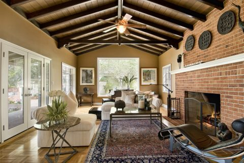 Beautiful living room with large brick fireplace, area rug, fan, french doors, windows and expensive furnishings, wood floor